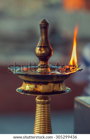 A five wick puja lamp for aarti in Hindu temple.  Puja is worship. Aarti is ritual of worship in which light or lamps are offered to the deities amid devotional songs and prayer chants. - stock photo