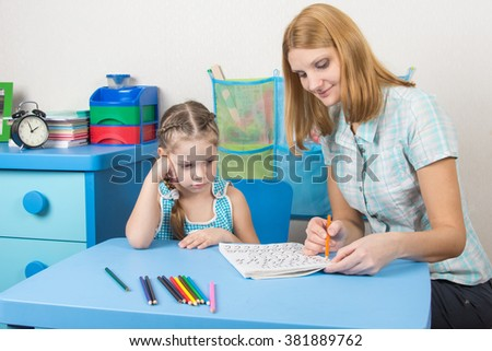 A five-year girl is engaged with adult young beautiful girl sitting at the children table at home - stock photo