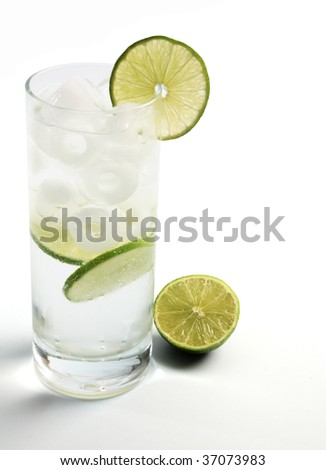 A fizzy mixed drink garnished with a lime, in a tall glass, isolated on white. - stock photo