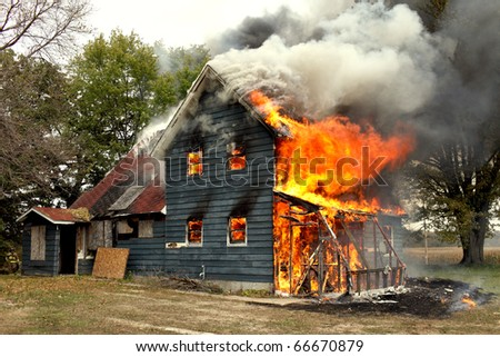 A flames of a raging fire engulf a house. - stock photo