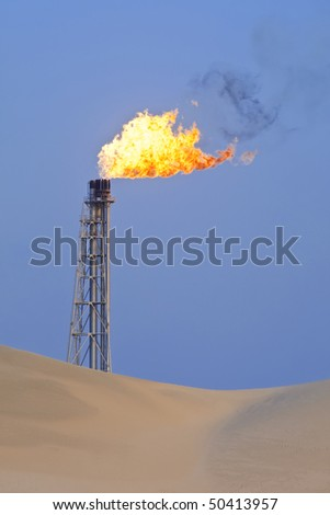 A flare stack burning off excess gas at an oil refinery in the desert