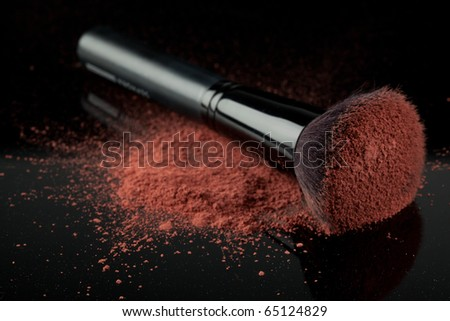 a flat blush brush with pink blush on it, placed on some loose powder blush, shot on black backgrownd. - stock photo