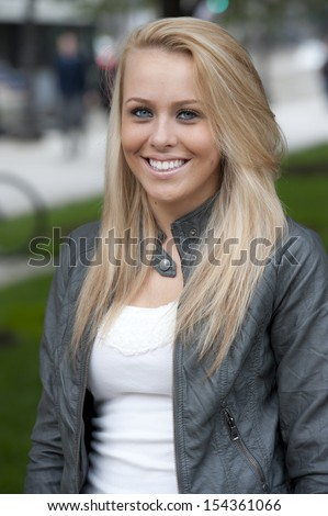 A flawless, young, blond, girl smiling outside on a chilly day. - stock photo