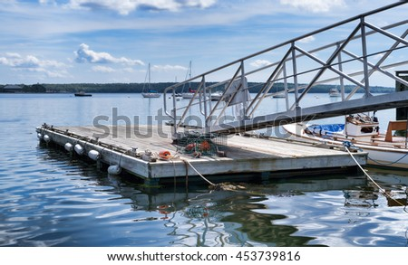 A floating dock with a lone lobster trap on the deck at Searsport, Maine