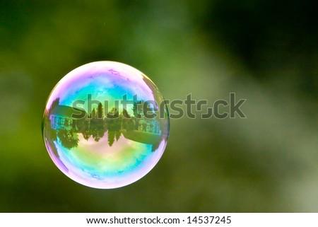 a floating soap bubble with the reflection of a house inside