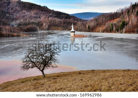 A flooded church in a toxic red lake. Water polluting by a copper mine. Rosia Montana, Romania - stock photo