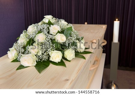 A flower arrangement on a coffin and a burning candle on the background in a mortuary - stock photo