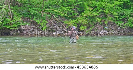 A fly-fisherman wading in deep water casts a fly in a clear river - stock photo