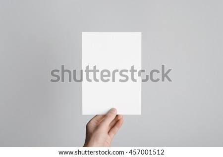 A5 Flyer / Invitation Mock-Up - Male hands holding a blank flyer on a gray background.