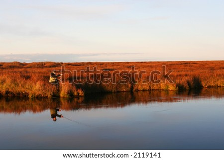 A flyfisher casting his line in a calm river in autumn - stock photo