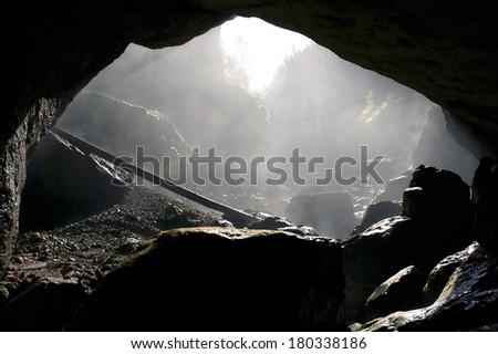 A foggy, dark cave entrance silhouette in Padis, Romania  - stock photo