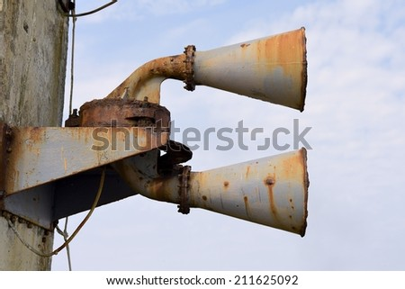A foghorn near to a lighthouse, corroded and rusty.