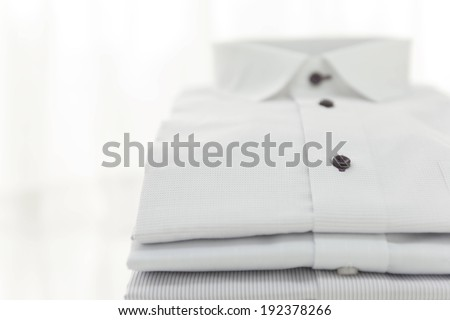 A folded white shirt with black colored buttons. - stock photo