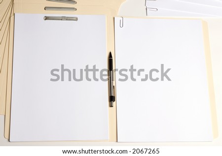 A folder lays open with blank paper on both sides. One cliped and one fastened - stock photo