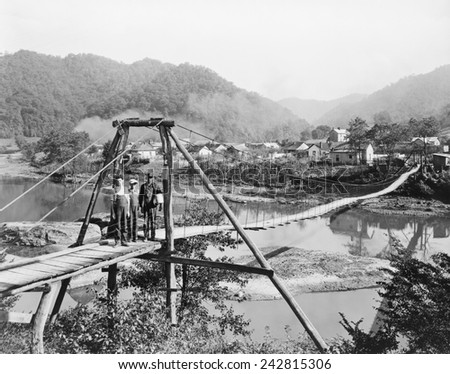 A foot bridge on the Cumberland River, Wilhoit, Harlan County, Kentucky in 1929. The mountainous county's economy was based on coal mining. - stock photo