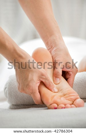 A foot massage being carried out in a spa by a masseuse - stock photo
