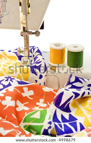A foot of a sewing machine and a couple of rolls of tread with colorful cloth - stock photo
