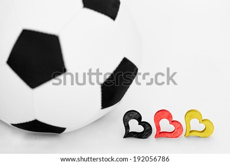 a football and three hearts in black, red, yellow - stock photo