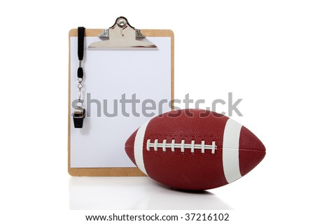 A football coaches clipboard with a whistle and an American football on a white background - stock photo
