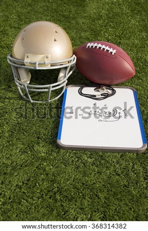 A football, helmet, clipboard and whistle on an artificial turf field.