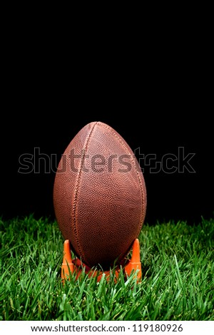 A football kickoff on a grass field with a black background to represent nighttime. - stock photo