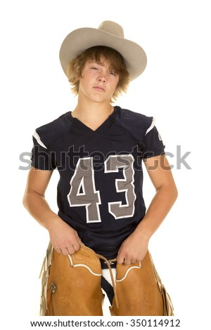 A football player with his jersey and cowboy hat on, with his chaps. - stock photo