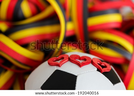 a football, three hearts and streamers in black, red, yellow - stock photo