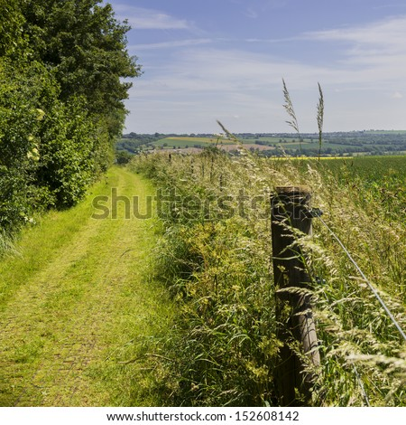 a footpath and public bridleway through the countryside - in the cotswolds, oxfordshire, england, uk - stock photo