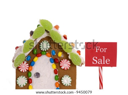 A 'For Sale' sign next to a gingerbread house. - stock photo
