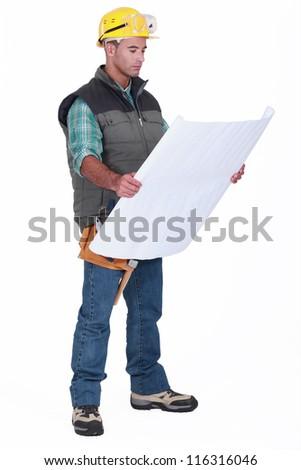A foreman checking blueprints. - stock photo