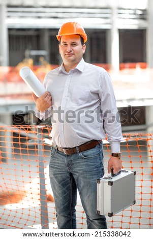 A foreman with drawings and case supervising the project at the construction. - stock photo