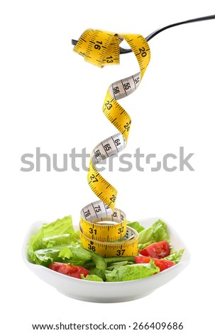 A fork holding a measuring tape from salad - health and diet concept - stock photo