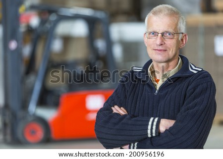 A forklift driver is posing in front of his forklift, he is a proffesional forkliftdriver, working in a warehouse.  - stock photo