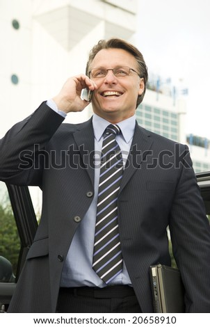 A forties businessman is standing in front of an office building and having a lighthearted conversation on his cellphone while holding his laptop computer - stock photo