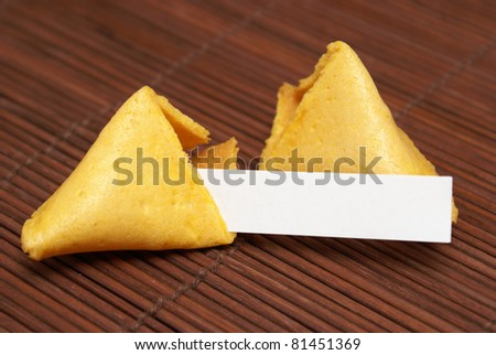 A fortune cookie with a blank paper for your message. - stock photo