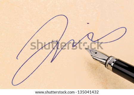 a fountain pen and a signature on yellow paper. symbolic photo for contract testament and graphology - stock photo
