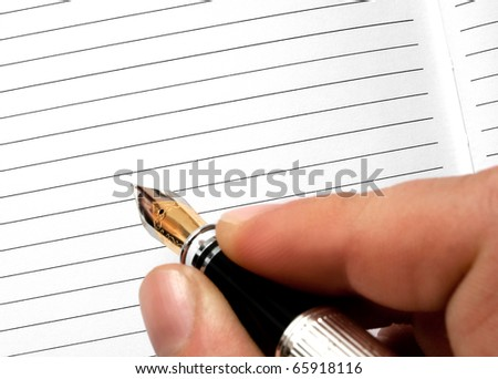 a fountain pen writing or signing on a blank agenda - stock photo