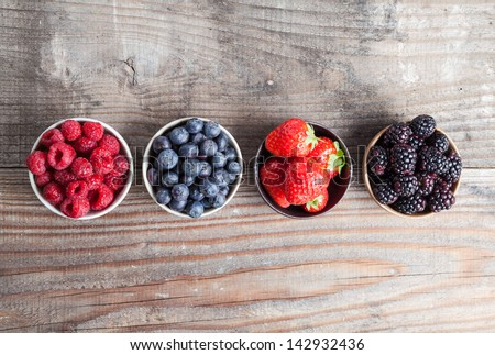 A four bowls overflowing with summer berries like strawberries, raspberries, blueberries and blackberries. - stock photo