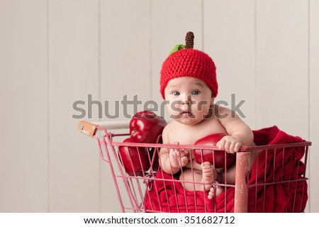 A four month old baby girl wearing a crocheted, apple hat. She is sitting in a little, vintage shopping cart. - stock photo