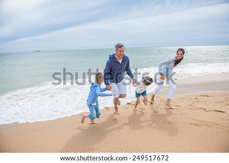 A four people family is playing in the sea waves, the parents and their two children are holding hands while running back from the sea waves  - stock photo