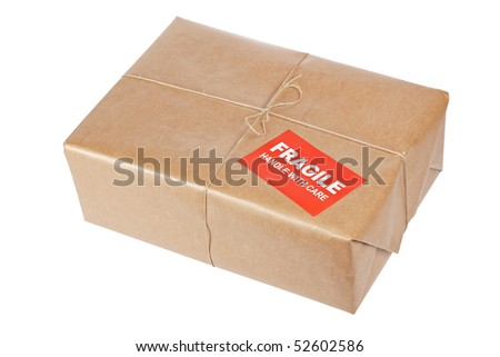 A fragile parcel wrapped in brown paper and tied with rough twine, isolated on white background. Shallow depth of field and path included - stock photo