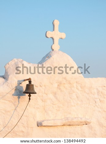 A fragment of an old white Greek  church with a cross and bell. - stock photo