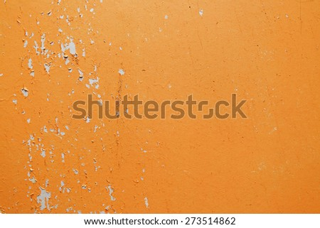A fragment of the old wall, painted bright orange paint, cracked over time. Peeling paint texture. - stock photo