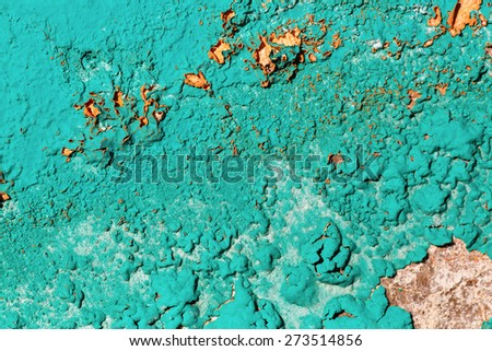 A fragment of the old wall, painted bright turquoise paint, cracked over time. Peeling paint texture. - stock photo