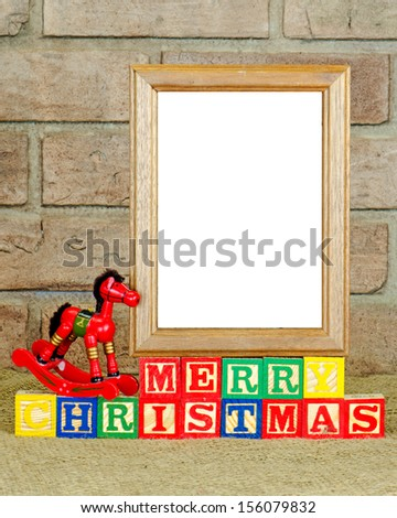 A frame with a blank panel on alphabet blocks spelling Merry Christmas