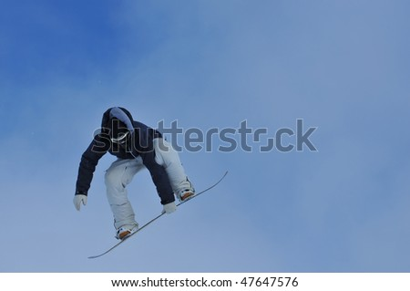 a freerider grabs his board during a jump - stock photo