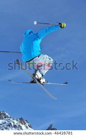 a freeriding ski jumper with crossed skis in blue clothes against a blue sky