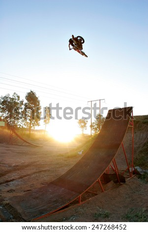 A freestyle motocross rider flies through the air above a ramp on his motorbike as the sun sets.
