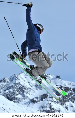 a freestyle skier touches his skis during a jump - stock photo