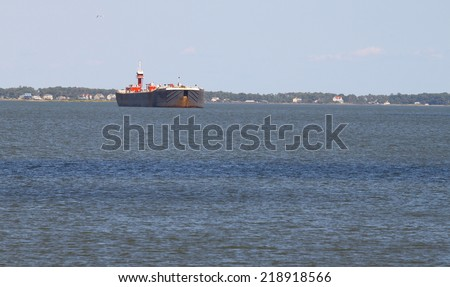 A freighter/tanker anchored off shore in the York river in Yorktown VA near the mouth of the York river and the Chesapeake Bay - stock photo